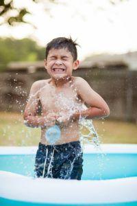 boy playing plastic balloon inside inflatable pool